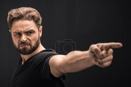 Photo for Angry bearded man pointing  isolated on black with copy space - Royalty Free Image