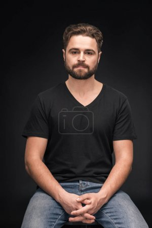 Photo pour Handsome bearded man sitting and looking at camera  isolated on black - image libre de droit