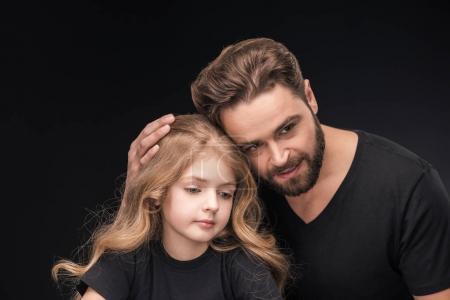 Photo pour Adorable petite fille et père étreignant son isolé sur noir - image libre de droit