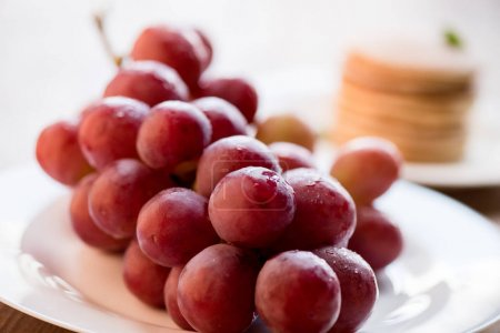 Photo for Close up view of fresh red grapes on plate, pancakes behind - Royalty Free Image