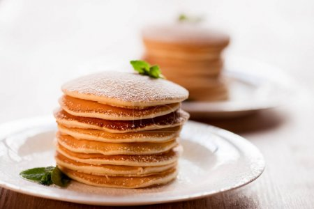 Tasty pancakes with mint and powdered sugar on whi...