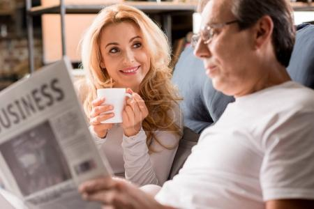 Photo for Happy middle aged couple sitting on bed, man reading newspaper at home - Royalty Free Image