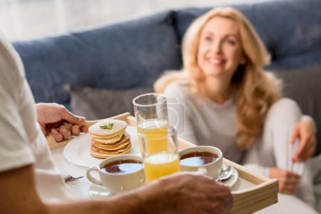 Photo for Man bringing tray with tasty breakfast to happy blonde woman on bed - Royalty Free Image