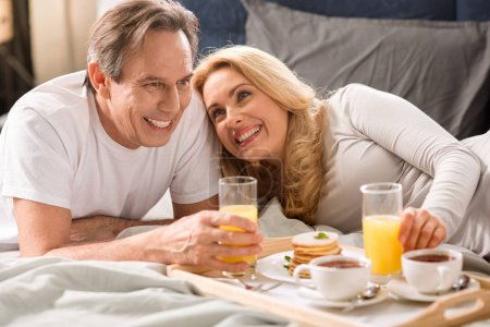 Photo for Happy middle aged couple having breakfast together in bed - Royalty Free Image