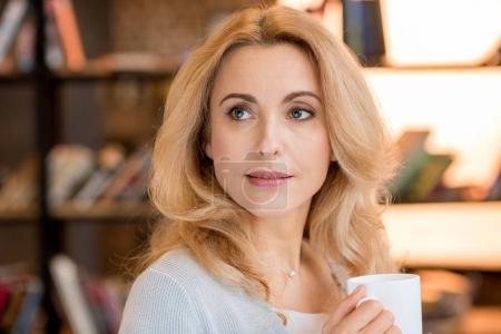 Photo for Beautiful blonde mature woman holding cup and looking away - Royalty Free Image