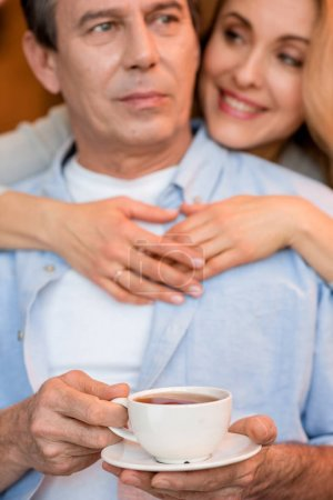 Photo for Beautiful smiling blonde woman hugging pensive mature man holding tea cup - Royalty Free Image