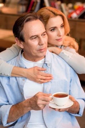 Photo pour Pensive couple d'âge mûr avec tasse de thé embrassant et regardant loin - image libre de droit