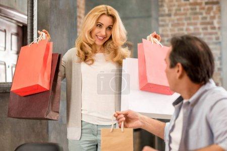 Photo pour Heureuse femme d'âge moyen tenant des sacs à provisions et regardant mari assis à la maison - image libre de droit
