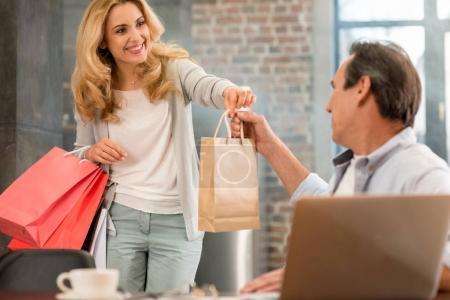 Photo pour Femme blonde heureuse tenant des sacs à provisions et donnant le sac en papier à son mari à la maison - image libre de droit