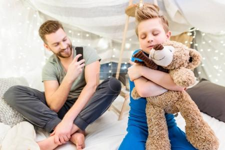Photo for Happy father using smartphone while little son hugging with teddy bear - Royalty Free Image