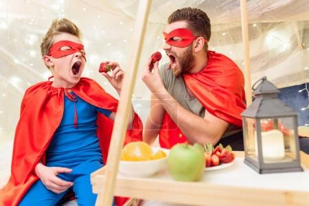 Photo for Happy father and son in superhero costumes eating strawberries in blanket fort - Royalty Free Image