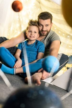 Foto de Padre e hijo sentados juntos en la fortaleza de la manta con la sistema solar modelo en primer plano - Imagen libre de derechos