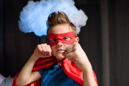 Photo pour Garçon en costume de super-héros rouge avec geste de combat en regardant la caméra - image libre de droit