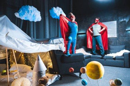 Photo pour Père et fils dans des costumes de super-héros rouge jouent à la maison - image libre de droit