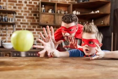 Photo pour Père et fils en costumes de super-héros rouge jouant avec la pomme - image libre de droit