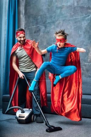 Photo pour Père en costume de super-héros aspirant tapis tandis que fils en costume de super-héros sautant - image libre de droit