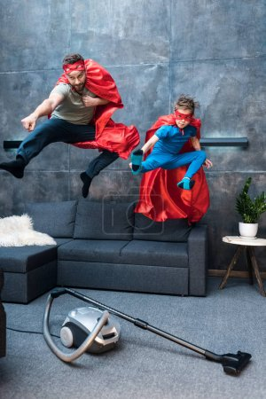 Photo for Father and son in superhero costumes jumping on sofa at home - Royalty Free Image