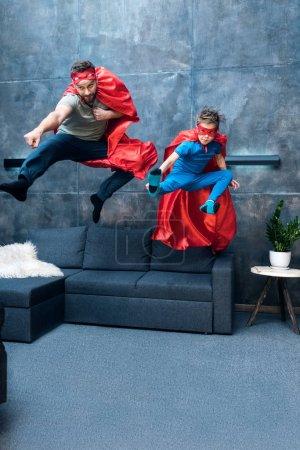 Photo pour Père et fils en costumes de super-héros sautant sur le canapé à la maison - image libre de droit