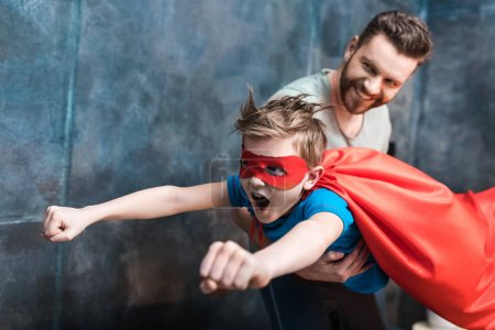 Father holding son in superhero costume flying at ...