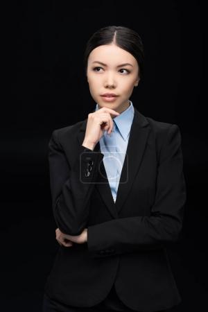 Photo for Brunette pensive businesswoman in black suit  isolated on black - Royalty Free Image