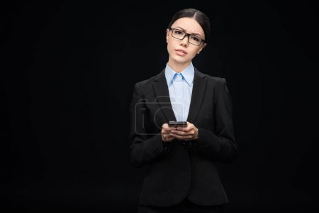 Photo for Brunette businesswoman in black suit using smartphone isolated on black - Royalty Free Image