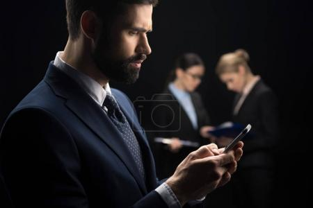 Photo for Businessman using smartphone while business people connecting behind isolated on black - Royalty Free Image