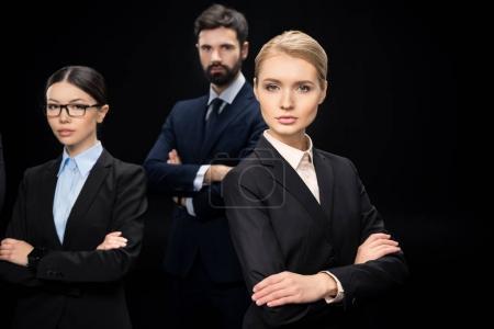 Photo pour Équipe d'affaires debout avec les bras croisés isolés sur noir, concept d'établissement d'entreprise - image libre de droit