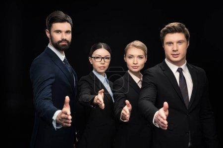 Photo pour Équipe d'affaires étirant les mains pour secouer isolé sur noir, concept d'établissement d'entreprise - image libre de droit