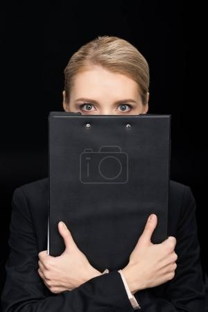 Photo for Businesswoman obscuring face with notepad isolated on black - Royalty Free Image