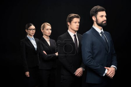 Photo for Side view of business people standing in row isolated on black - Royalty Free Image