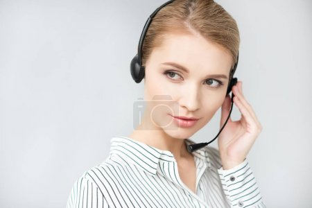 Photo for Portrait of young call center operator in headset isolated on grey - Royalty Free Image