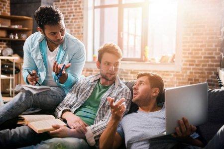 Photo pour Jeune groupe professionnel assis ensemble sur un canapé avec ordinateur portable et discuter - image libre de droit