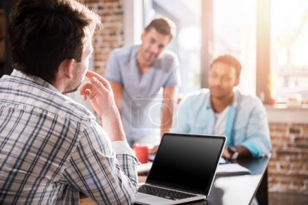 Photo for Young man using laptop while colleagues discussing project, small business meeting concept - Royalty Free Image
