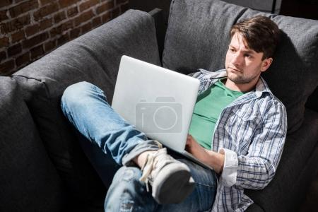 Photo for Serious young man lying on sofa and using laptop at home, small business people concept - Royalty Free Image