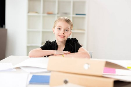 Photo for Little girl  sitting at table with papers in bright white room - Royalty Free Image