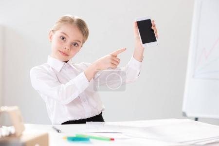 Photo for Cute little girl in formal clothes pointing at smartphone on white background - Royalty Free Image