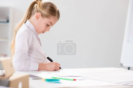 Photo for Serious little girl writing at table, in bright white room - Royalty Free Image