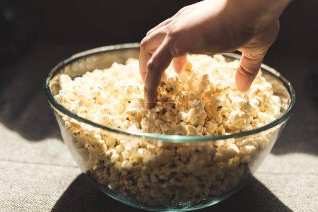 human hand taking popcorn