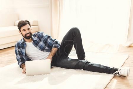 man lying on carpet and using laptop