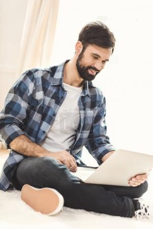 Man sitting on carpet and using laptop