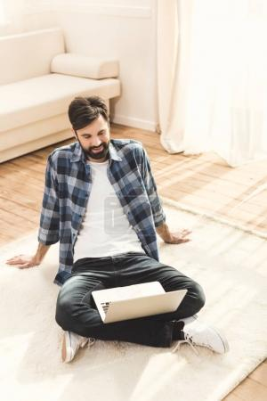 Man sitting on carpet and looking at monitor