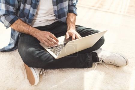 Homme assis sur le tapis et tapant sur ordinateur portable