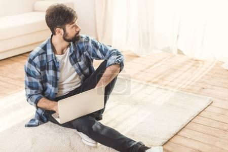 Thoughtful man sitting on carpet and daydreaming