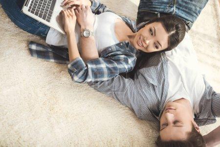 Photo pour Femme heureuse allongée sur son petit ami et utilisant un ordinateur portable - image libre de droit