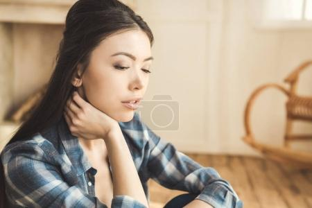 Photo for Portrait of young engrossed woman daydreaming with hand on chin - Royalty Free Image
