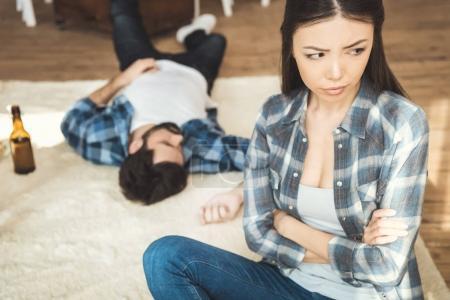 woman sitting on floor near drunk boyfriend