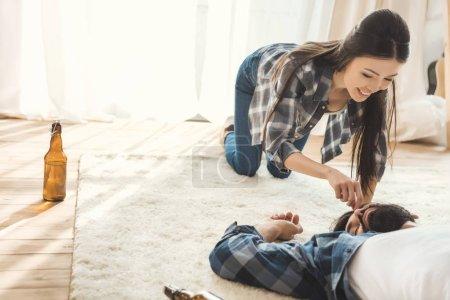 Woman having fun with sleeping boyfriend