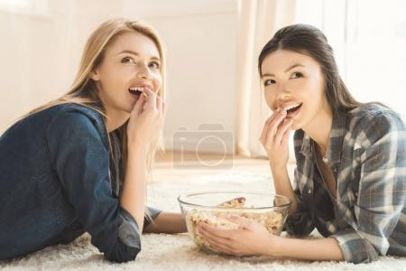Photo for Side view of two young women lying on carpet and eating popcorn - Royalty Free Image