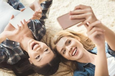 Photo for Overhead view of two women taking selfie while lying on floor - Royalty Free Image