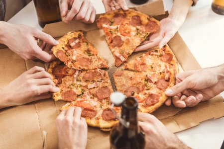 Human hands holding slices of pizza